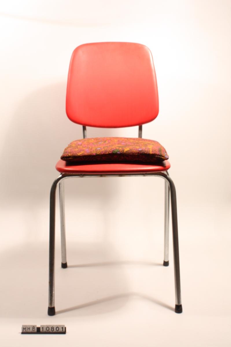 Stol  med plastsete og -rygg. Svarte plastknotter nede på beina. Sydd pute med mønstret trekk. Festet med strikk rundt stolryggen.