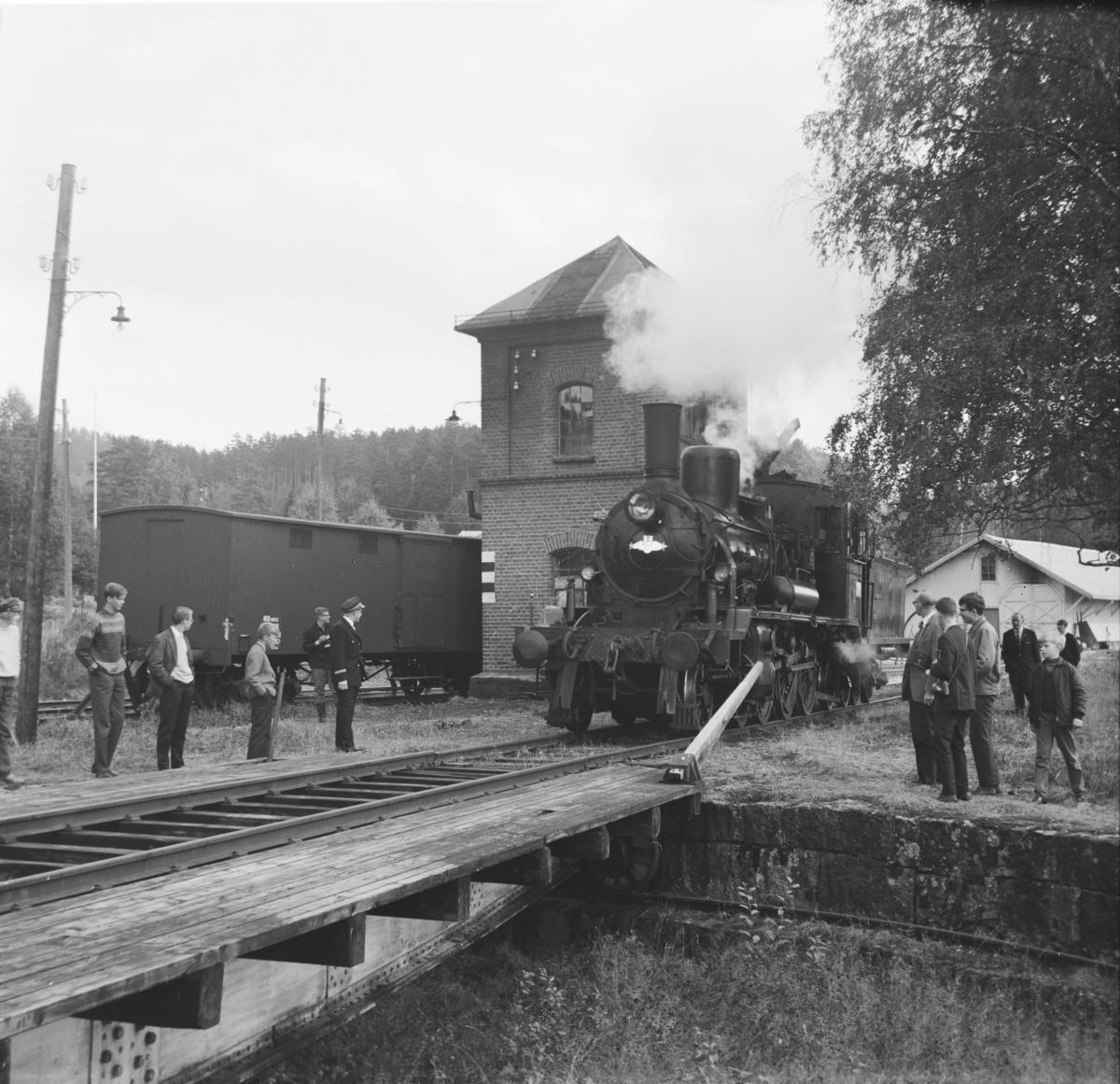 A/L Hølandsbanens veterantog har ankommet Krøderen stasjon. Damplok 18c 245 ved vanntårn og svingskive.