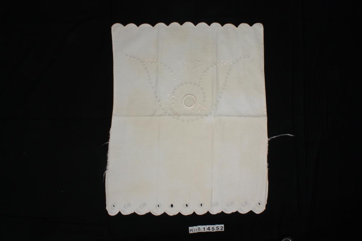 """Pyntetekstil brodert med engelsk hullsøm, hvitt på hvitt.  Initialene""""N T"""" er brodert med slyngornametikk i hovedbroderiet.   Dobbelt tekstil, der hovedbroderiet er kun på den ene delen. Disse to tekstildelene er sydd sammen på tre sider, mens siste kortside er åpen."""