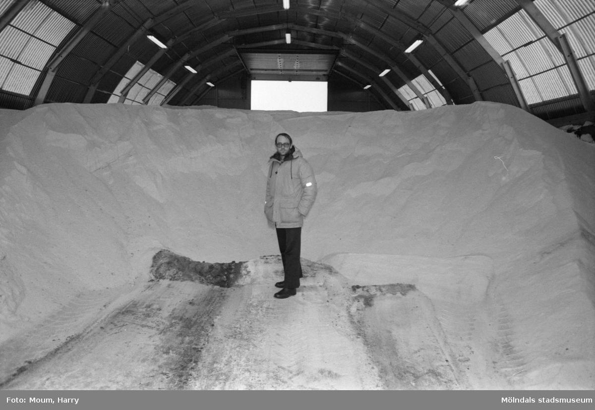 """Gatukontorets centralförråd vid Skedebrogatan i Mölndal, år 1985. """"Förrådschef Gunnar Wigén i """"saltlådan"""" där det förvaras hundratals ton salt, flis och sand.""""  För mer information om bilden se under tilläggsinformation."""