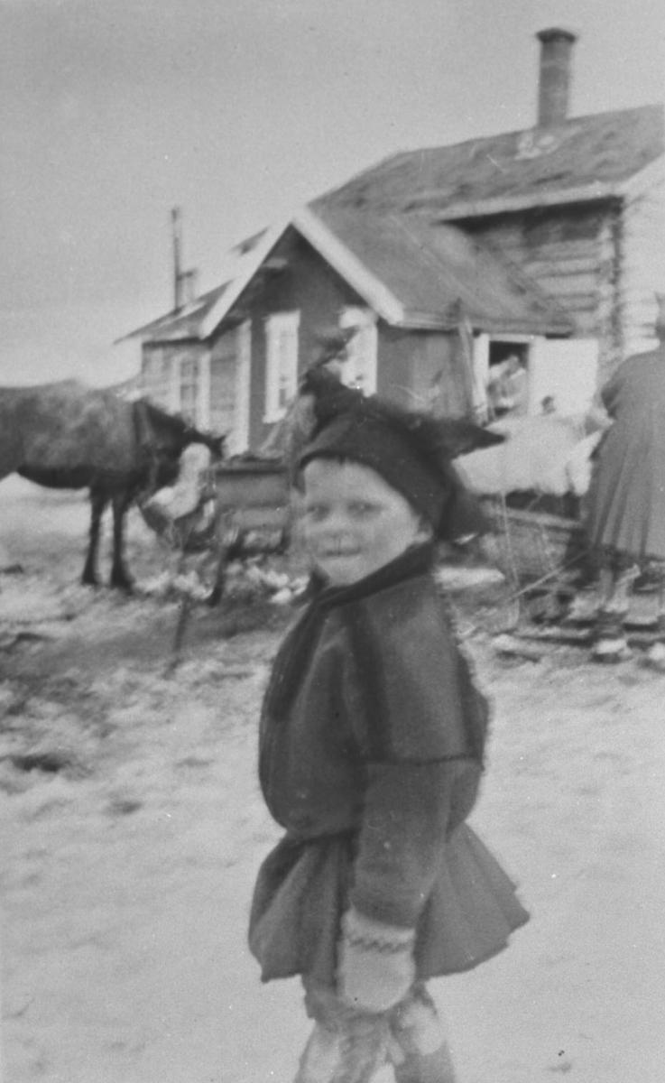 Liten samegutt, Ole Olsen, står på gata trolig i Karasjok. På bakgrunn står det et hus og foran huset en hest med slede. Bildet er lite uskarp, men ellers fin.