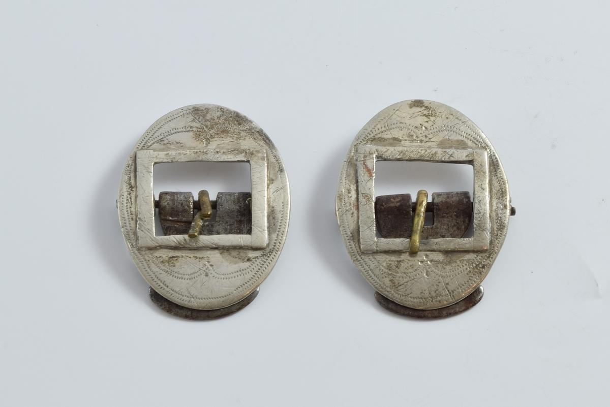 To spenne, spretter, del av belte ble brukt til å holde strømper oppe (folkedrakt fra Setesdal). Platene er prydet med innprikkede linjer,