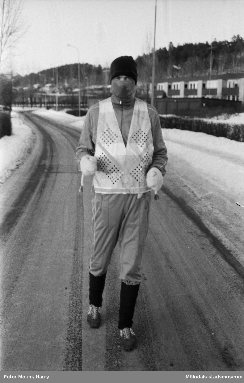 """""""Jan Lindström, Lindomebo ute i svinkylan på en träningsrunda. Bortåt tre mil avverkar han under ett pass. För säkerhets skull bör han lägga rutten på behörigt avstånd från bank och postkontor. Träningsmunderingen liknade mest av allt en rånares."""" Rävekärr i Mölndal, år 1985.  För mer information om bilden se under tilläggsinformation."""