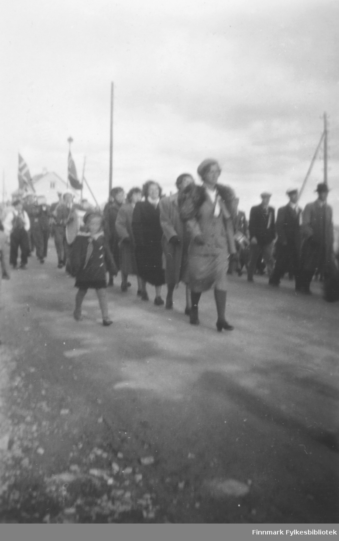Dette ser ut til å være kor som marsjerer i Vadsøs gater. Bildet kan være tatt en 17. mai på slutten av 1940-tallet. Kvinnene går nærmest kamera, mennene lengst borte. Alle har sangerluer på