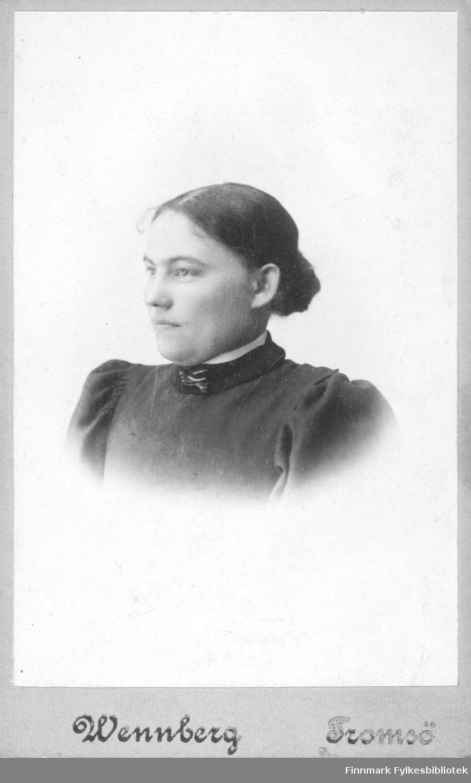 Portrett av en ung kvinne, navn ukjent. Hun har en sort kjole med en hvit liten blusekant øverst, halslinningen er pyntet med en liten nål som ser ut til å være en liten fugl. Bildet er tatt hos fotograf Wennborg i Tromsø.