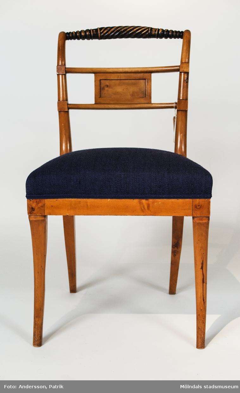 """Stol av polerad björk med svärtade partier. Tillverkad i Lindome omkring 1820. Svarvad överliggare med en sprialvridet mittparti, som påminner om en repstump. Liten rektangulär ryggbricka inplacerad mellan två horisontella spjälor. Sabelformade framben. Fast stoppad sits klädd med blå- och beigerandigt tyg.Brännstämplad i baksargen """"AES:H."""" - Andreas Ericsson, Hassungared 1 (1790-1871).Stoltypen är vanlig i lindomeproduktionen omkring 1820 och kallas vanligen för """"Trafalgarmodell"""" då den återgår på en engelsk stol som tillverkades för lord Nelson mäss på skeppet Victory.Stolen är i par med MM02392."""