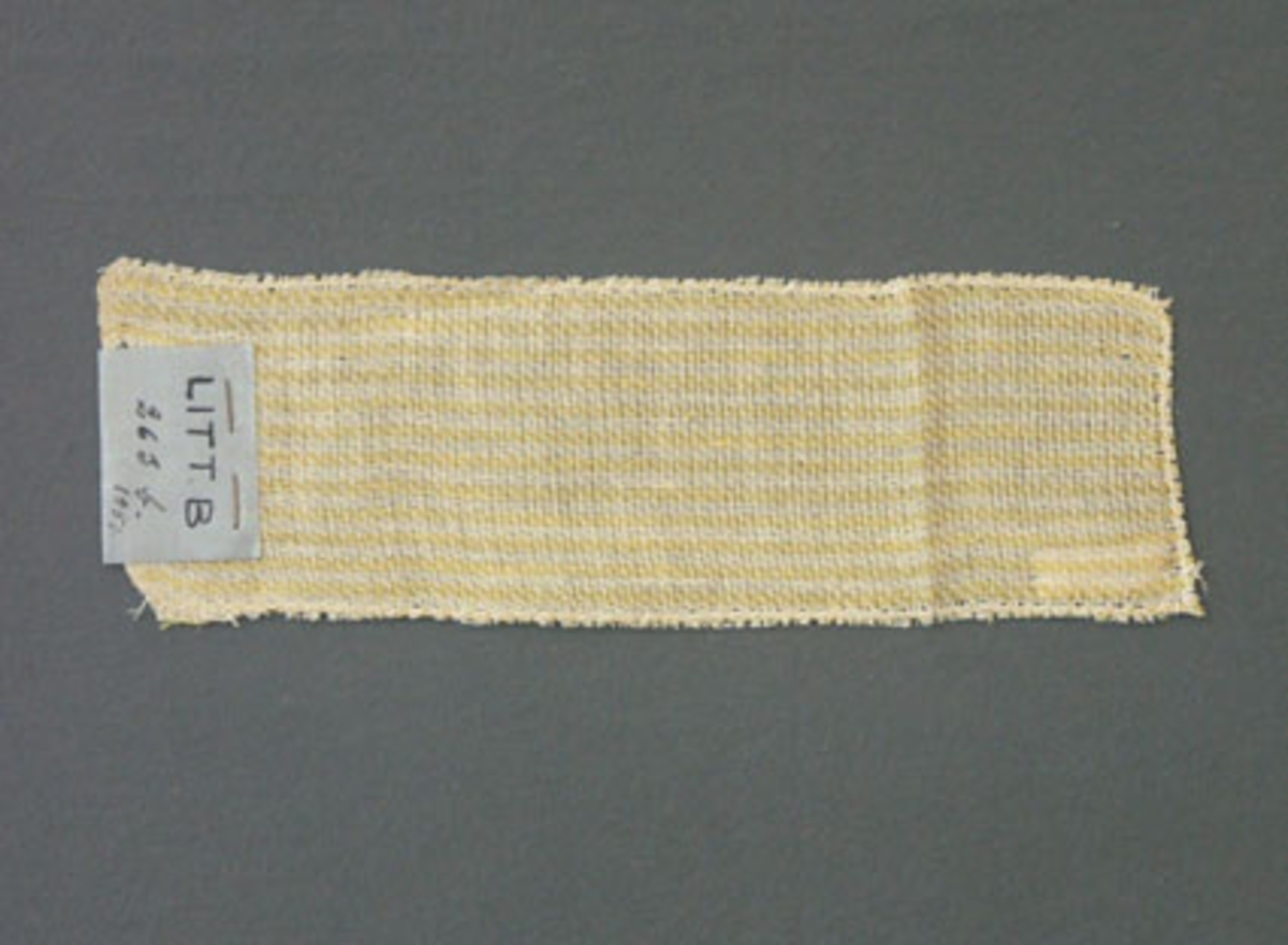 Prov till gardin vävd i kypert. Provet har bomullsgarn i varp och lingarn i inslag.Ytterligare prov och vissa vävuppgifter finns i pärm gardiner A, litt B 263 b.