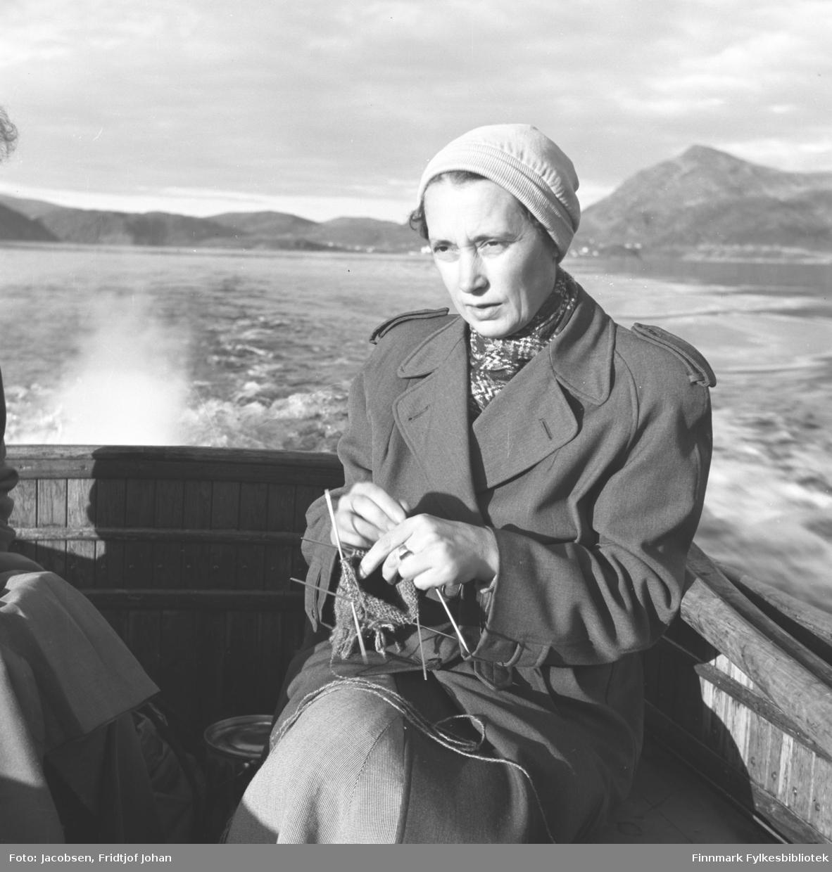 Aase Jacobsen med strikketøyet på båttur i Sørøysundet. Hun sitter på båtdekket iført en ganske mørk kåpe med skjerf i halsen og lys lue på hodet. Kjølvannet og eksosen ses bak henne og bygningene som står i bakgrunnen er Rypefjord.