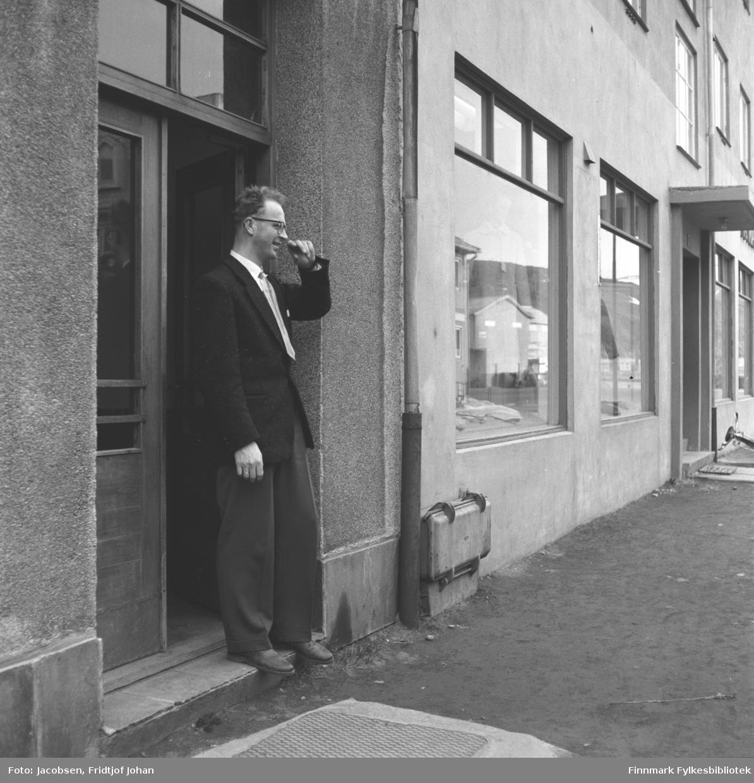 Arvid Solberg i døråpningen på bygget til gamle Sparekassen i Sjøgata. Han har en mørk/svart dress på seg med hvit skjorte og slips. Døra bak han er mørk og to-delt med sprossevindu øverst. Det er murvegger på denne og nabobygningen. Store vinduer på gateplan ses på veggen langs det grusdekte fortauet. Innenfor var Maia Mathisens Manufaktur.