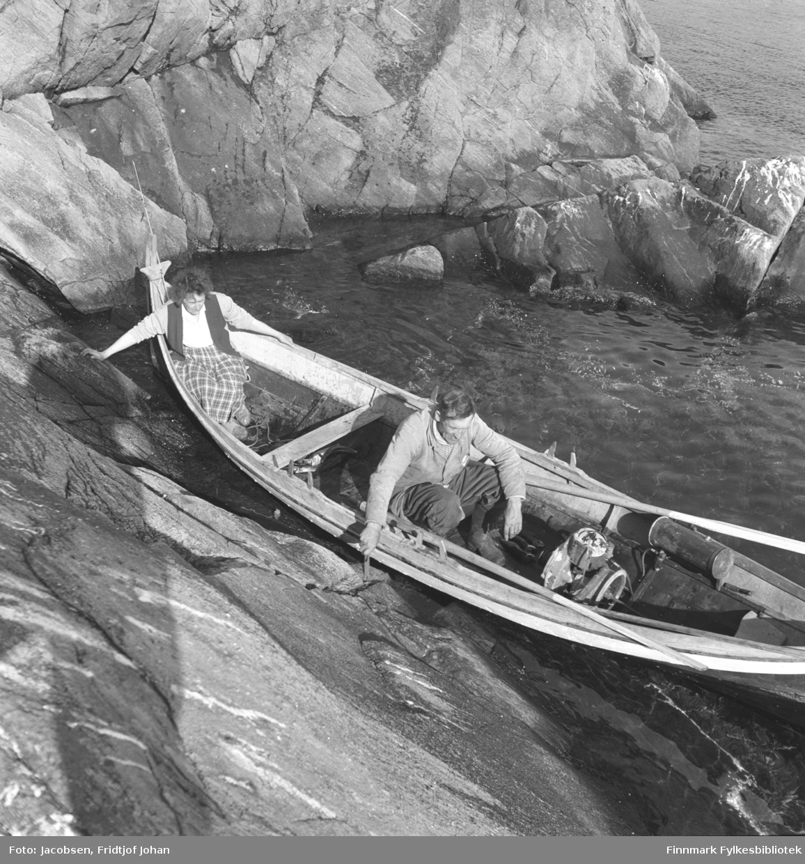 Arne Nakken og datteren Aase Randi Jacobsen på båttur i Arnes Nordlandsbåt. Aase har et rutet skjørt, hvit genser og mørk vest på seg. Arne har en lys genser og noe mørkere bukse. Årer ligger inni båten langs rekka og i midten står en liten båtmotor. Båten ligger inntil et berg i en kjeile. Litt skum fra bølger som har slått mot berget ses på sjøen.