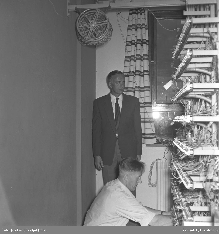 Fra automatiseringen av telefonsentralen i Bossekop i Alta. Alf Aleksandersen arbeider med hovedkoplingsstativet. Han har en hvit, kortermet skjorte på seg. En mann står litt bak på bildet. Han har en mørk dress med hvit skjorte og slips på seg. Et vindu står på veggen i bakgrunnen og stripete gardiner henger foran det.