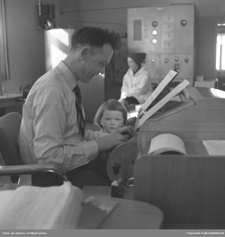 Karstein Ramme arbeider med sin lille datter ved siden av. I bakgrunnen sitter en kvinne, dette kan være hans kone fra Komagfjord, eller det kan være Aase Jacobsen