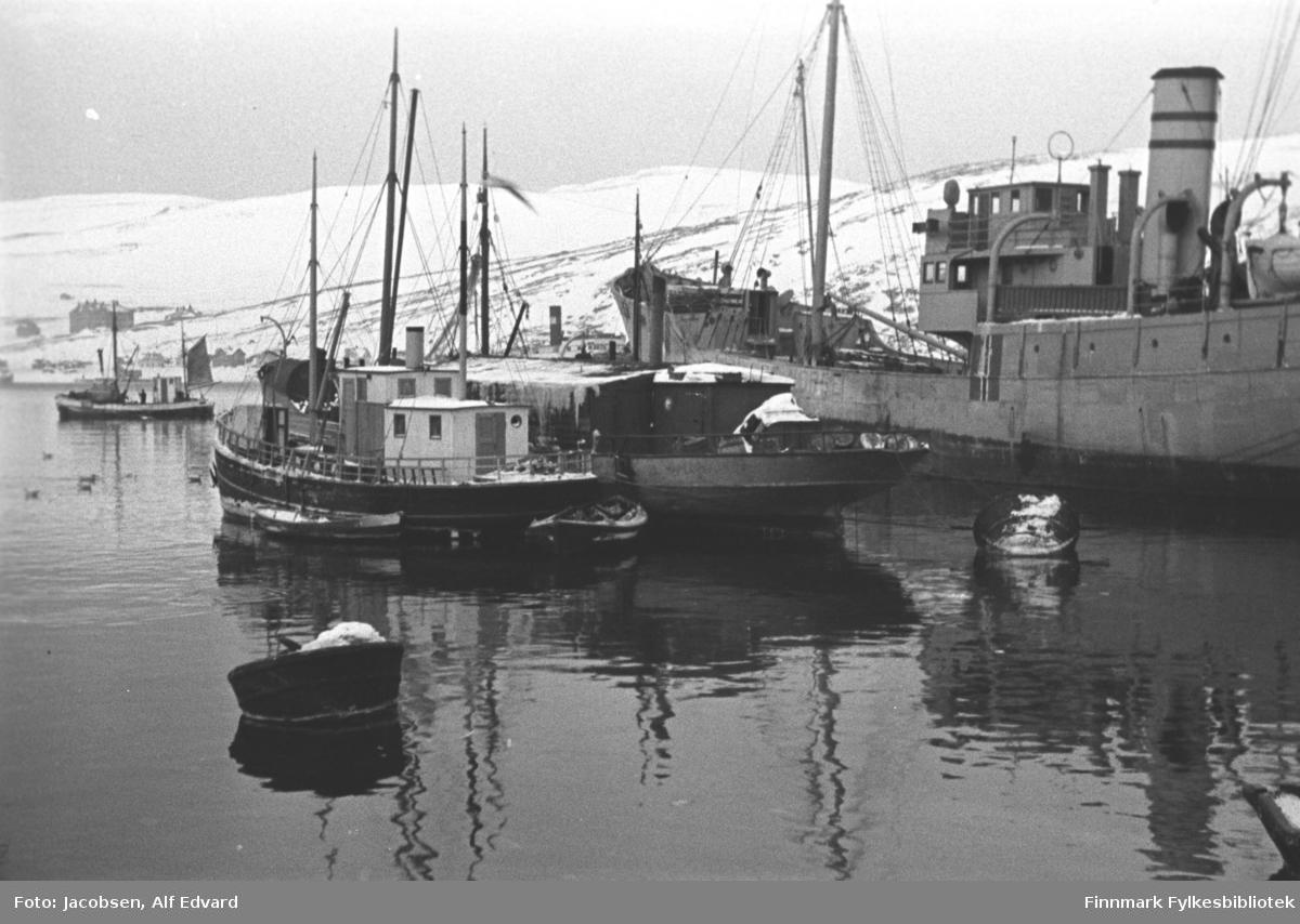 Blikkstille på havna i Hammerfest en vinterdag under krigen. Nærmest, til venstre på bildet ligger lensmannsbåten Streif. Den har sort/mørkt skrog og hvitt/lyst rorhus. En rund, ganske lav skorstein med en mørk stripe står på taket. Fartøyet har en mast foran med bom/vinsj. To lettbåter ligger inntil den, en på siden og den andre ved hekken. En større båt ligger ved siden av. Den er trefarget, har en hvitmalt, bred rekke og et flatt overbygg på dekk. Helt til høyre på bildet ligger en mye større båt, muligens en fraktebåt. Hele båten er gråmalt med det norske flagg malt midtskips. En tykk mast med lastebom og tauverk som går fra toppen og mot rekka, står på dekket foran. Rorhuset står midt på båten med en stor skorstein like bak. Skorsteinen har to malte, mørke striper oppe. Baugen på en livbåt ses helt til høyre på bildet. Lenger ute på havna ligger en fiskebåt med mesanen heist. To personer står på dekket foran det hvitmalte rorhuset. Det store bygget til venstre på bildet, som vises mot Storfjellet, er sykehuset. Noe av bebyggelsen ses langs Fuglenesveien. En god del snø ligger i terrenget.