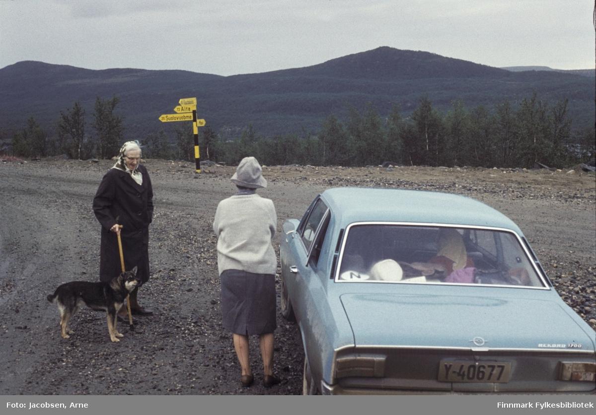 Olga og Aase Jacobsen i nærheten av Masi. Olga med stokk og en hund ved siden av seg. Hun har en mørk kåpe og tørkle. Aase har skjørt, lys jakke og hatt. Bilen de står utenfor er en Opel Rekord (modell C, kom ny som årsmodell 1967 og gikk til ca. 1971) og veien har grusdekke. Skogkledd terreng med fjellknauser i bakgrunnen. Et skilt med avstandene til Alta, Suolovuobme og Masi står i veikanten. Saker og ting ligger i hattehylla.