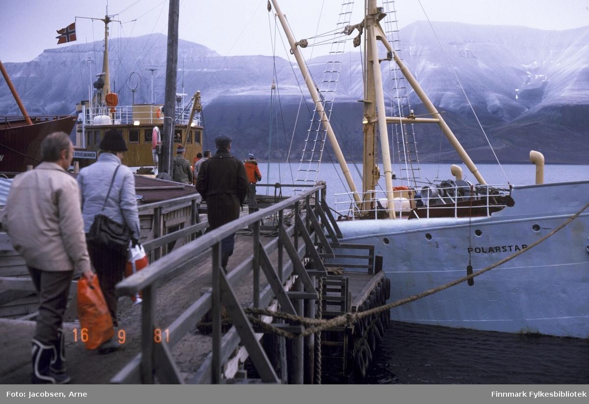 Selfangstskuta M/S Polarstar ved kai. Flere personer er på tur ombord fra en trekai. De to bakerste med plastposer i hendene og en har en veske over skulderen. Flere av personene har luer på.  Midt på bildet ses en tykk mast med vinsj-arm og leidere som går ned på begge sider. Foran masta står ankervinsjen med trommel. Båten har det norske flagg i masta på rorhustaket. Helt til venste stikker baugen på en annen båt frem og til høyre går fortøyningstampen fra baugen av skipet til kaia. I bakgrunnen ligger høye fjell.
