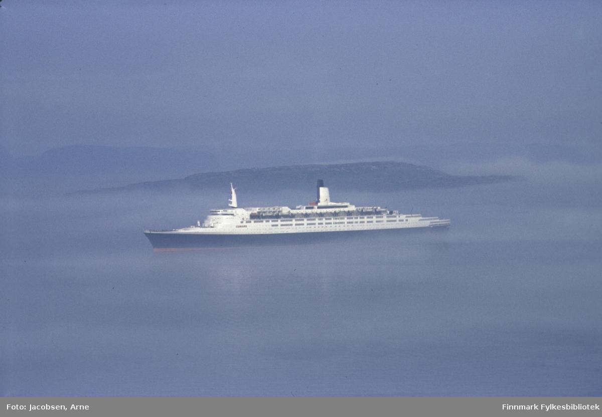 """Passasjerskip """"MS Queen Elizabeth 2"""" på vei ut fra Hammerfest. Det er endel tåke, men Melkøya vises bak skipet og Sørøya kan såvidt skimtes bak Melkøya. Melkøya huser i dag Snøhvit-anlegget. Været er fint og solen er i ferd med å bryte gjennom tåke-/skylaget."""