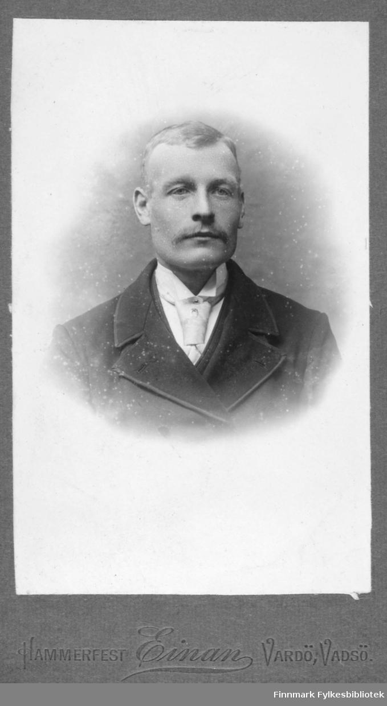 Portrett av en ukjent mann. Han er kledt i en mørk jakke og hvit skjorte. I halsen har han et lyst slips