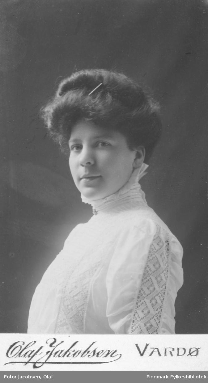 Portrett av ukjent kvinne. Hun er kledt i en høghalset hvit kjole eller bluse med innfelt blonder