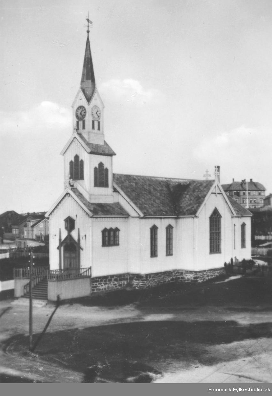 Fotografi av Vardø Kirke som var tegnet av Chr. H. Grosch og bygd i 1869. Langkirken ble brent under annen verdenskrig. Til høyre bak kirken kan vi se en del av Vardø gamle barneskole som ble tatt i bruk i mars 1888. Flagget er heist i flaggstanga. Til venstre er det flere trebygninger som ligger langs gaten