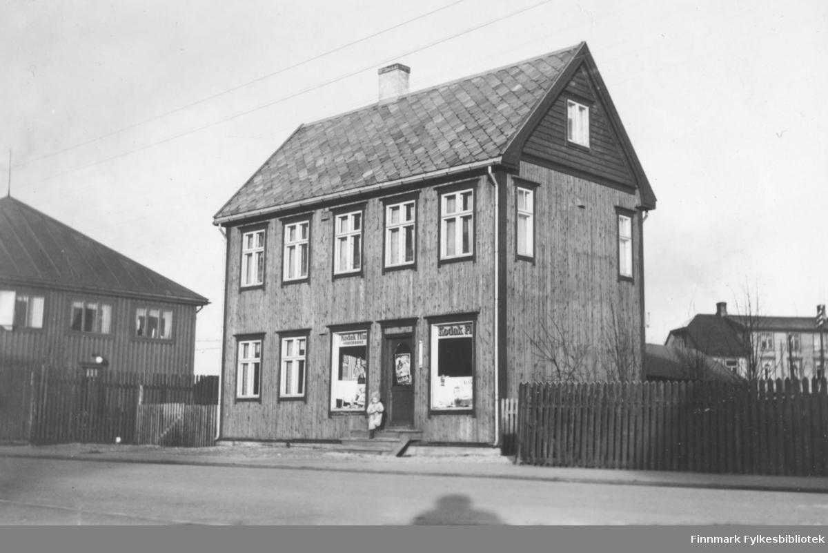 Fotografi av Olaf Adolf Jacobsens fotoforretning i Kirkenes. Huset er en to etasjes trebygning med loft. Fotoforretningen ligger i første etasje. I vinduene er det reklame for Kodak film. På trappen står det et barn. Omkring huset er det gjerde. Til venstre og høyre ser man to bygninger