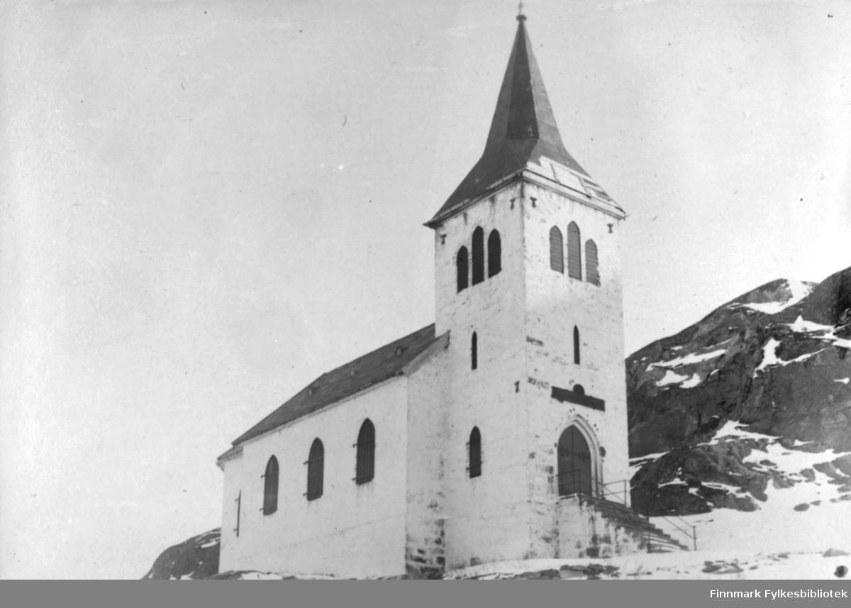 Fotografi av Kong Oscars ll kapell i Grense-Jakobselv. Kirken er bygd i 1869. Kong Oscar II besøkte kirken i 1870 årene, og siden da har kirken båret hans navn. Kirken er bygd på en fjellknaus. Frem til 1969 var kirken hvitkalket som vist på bildet og tjente som et landemerke. Etter sandblåsingen kom gråsteinen som kapellet er bygd av fram. Det ligger snø rundt kirken og på fjellet i bakgrunnen