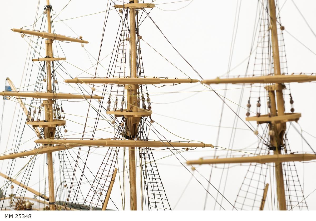 """Fullriggat segelfartyg. Skrovet i huvudsak vitt men med en röd rand nära relingen. SKrovet under vattenlinjen också målat i rödbrun färg. Längs skrovets långsida sitter ventiler.   I aktern hänger tre skeppsbåtar, en längs med akterspegeln och de övriga två vid låringarna. Skeppsbåtarna är vita men med röd bottenfärg. Mellan fock- och stormasten står ett däckshus i brungult med bruna knutar och inlägg, däri har byssan rymts. På däckshuset sitter frälsarkransen och ventiler. För om fockmasten två vita däckshus vid relingen på varsin sida. Under peket ett nät. Akter om kryssmasten syns en dubbeldrill och ett nakterhus.   Modellen är monterad på en träplatta i märkt lackat trä. På träplattan en blå skylt med text: """"NAJADEN""""."""