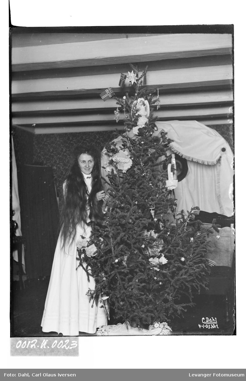 Lil med utslått hår, hvit kjole og juletre