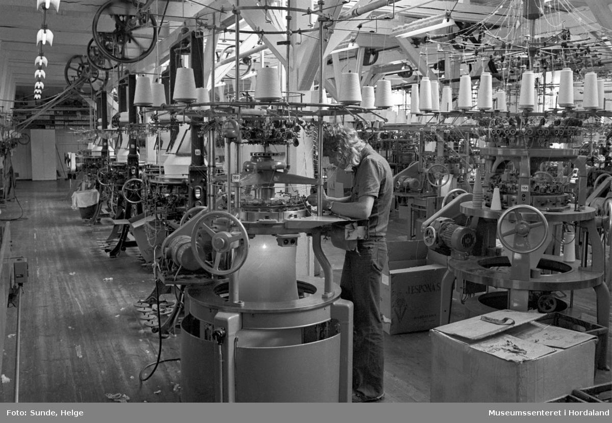Arbeidsliv ved Salhus Tricotagefabrik i Salhus, Bergen i 1976. Arbeidar ved strikkemaskin på strikkeloftet ved Salhus Tricotagefabrik.