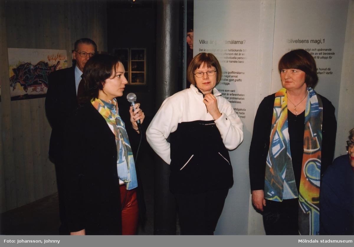 """Kvinna håller tal i utställningen """"Alltså finns jag"""" på Mölndals museum, år 2003. Till höger ses museichef Mari-Louise Olsson.  Utställningen """"Alltså finns jag"""" ...en utställning om graffitikultur på Mölndals Museum, Kvarnbygatan 12, Mölndal, pågick från 25 januari till 25 maj 2003.  """"Alltså finns jag"""" var ett samarbete mellan Mölndals museum, Vitlycke museum, Bohusläns museum, Västergötlands museum och Konstkonsulenterna i Västra Götalandsregionen."""