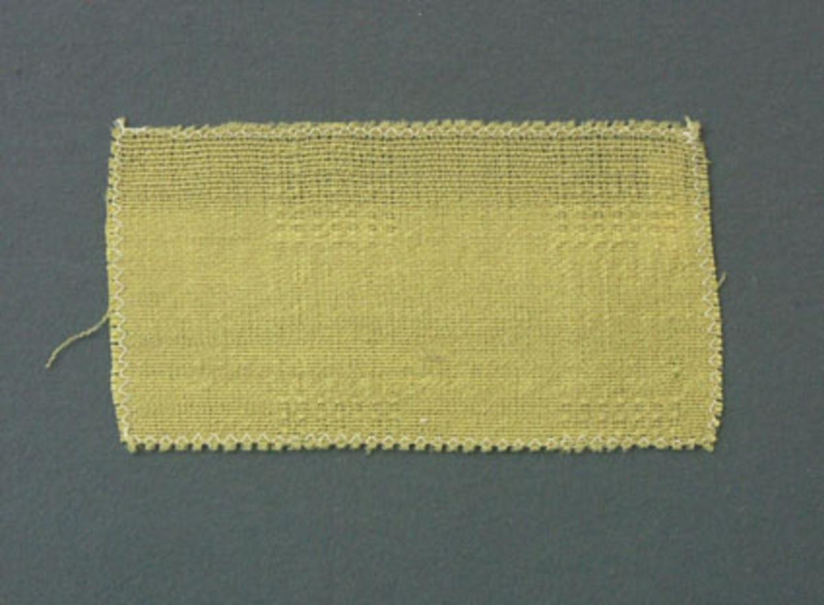 Prov till gardin vävd i tuskaft och stramalj.  Provet har ullgarn i varp och inslag.
