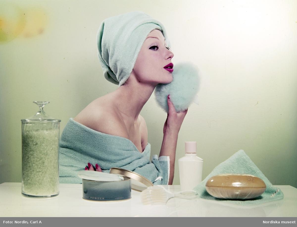 Modell med turkos handduk på huvudet och runt kropppen använder en puderpuff i ansiktet. Skönhetsprodukter på bordet.