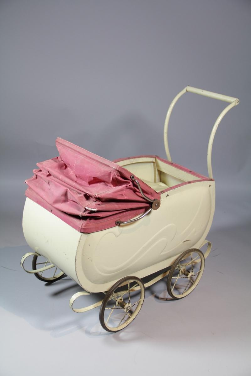 Lav dukkevogn i hvit med rosa kalesje. Selve vognen er i tynn, hvit finer, med metall understell, hjul og håndtak. Uttrekkbar kalesje i vinylstoff/teltduk med metallspiler. innhold i form av en madrass, en pute, en dyne, begge i rosa satengstoff med vattfyll, et putetrekk og dynetrekk i tynt, hvitt, gjennomsiktig stoff.