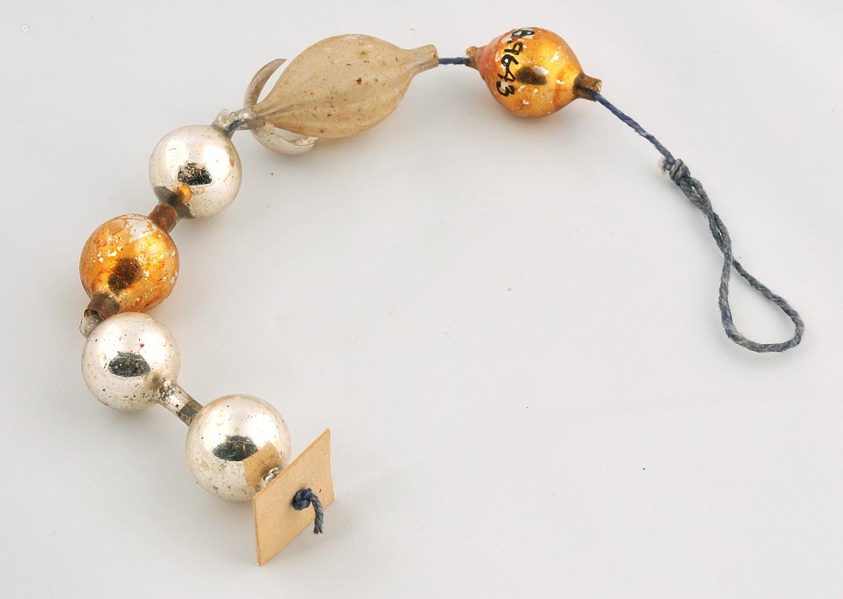3 blanke sølvfarga kuler, 2 blanke bronsefarga og 1 matt oval kule med striper som er tredd inn på ein bomullstråd så det dannar eit kjede.