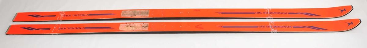 Hoppski laga av glasfiber. Oransje overside, svarte sidekantar Kvit plastsåle med namnet Kongsberg ski synleg gjennom plastbelegget, 6 riller på midten av såla. Metallbeslag på baktuppane. Det er bora hol til bindingar.
