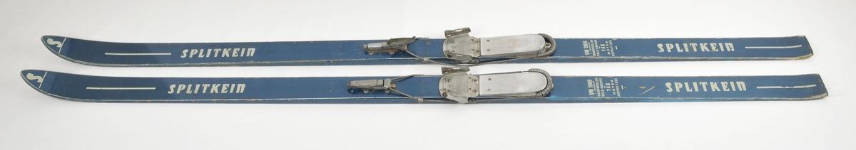 Hoppski laga av tre. Blå overflate, S-emblem på skitupp. Grå plastsåle med fem riller. Påsatt Kandahar bindingar,Gressvik. Solid hælsåle av metall. Bruksslitasje.