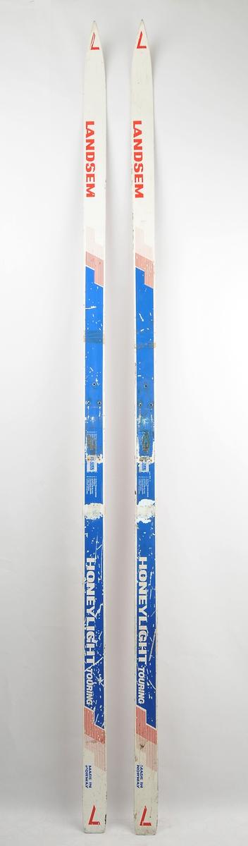 """Langrennski laga av glasfiber. Kvit overflate med blå og raud dekor/skrift, raud såle av plast. Det har vore bora hol til bindingar. Bruksslitasje, den eine skia er broten slik at ein kan sjå """"honeycomb"""" kjerna av aluminium."""