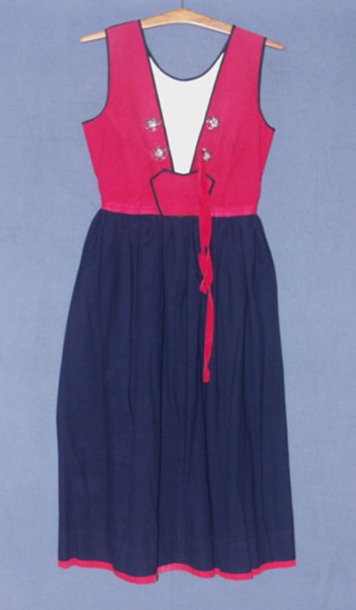 Livkjol till Värendsdräkten med kjol i blått kläde och liv i rött kläde. Livet har en smäck, eller bröstlapp, och är fodrat med ett halvblekt bomullstyg och kantat med svart sidenband. På livet är fyra silverbucklor fastsydda och genom den ena är trätt ett rött band till snörning, bandet är troligen av silke och bomull.Kjolen är rynkad i linningen och ihopsydd med livet med ett rött bomullstyg. Smäcken knäpps med tryckknappar och kjolen med hyskor och hakar. Kjolen är nedtill kantad med ett rött bomullstyg.I linningen är fastsytt en etikett från Kronobergs hemslöjd Växjö.