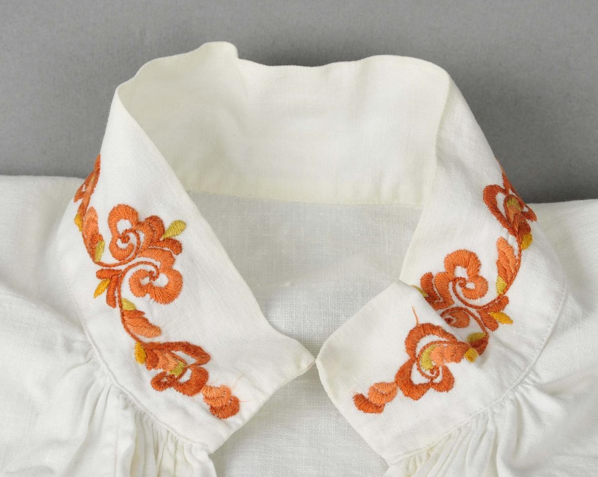 Skjorte i primærsnitt med kulørt rosesaum på hals- og armliner. Heil opning i front. Armane er rynka ved linene. Lask under armane, tre legg på kvar side av armpåsettinga.