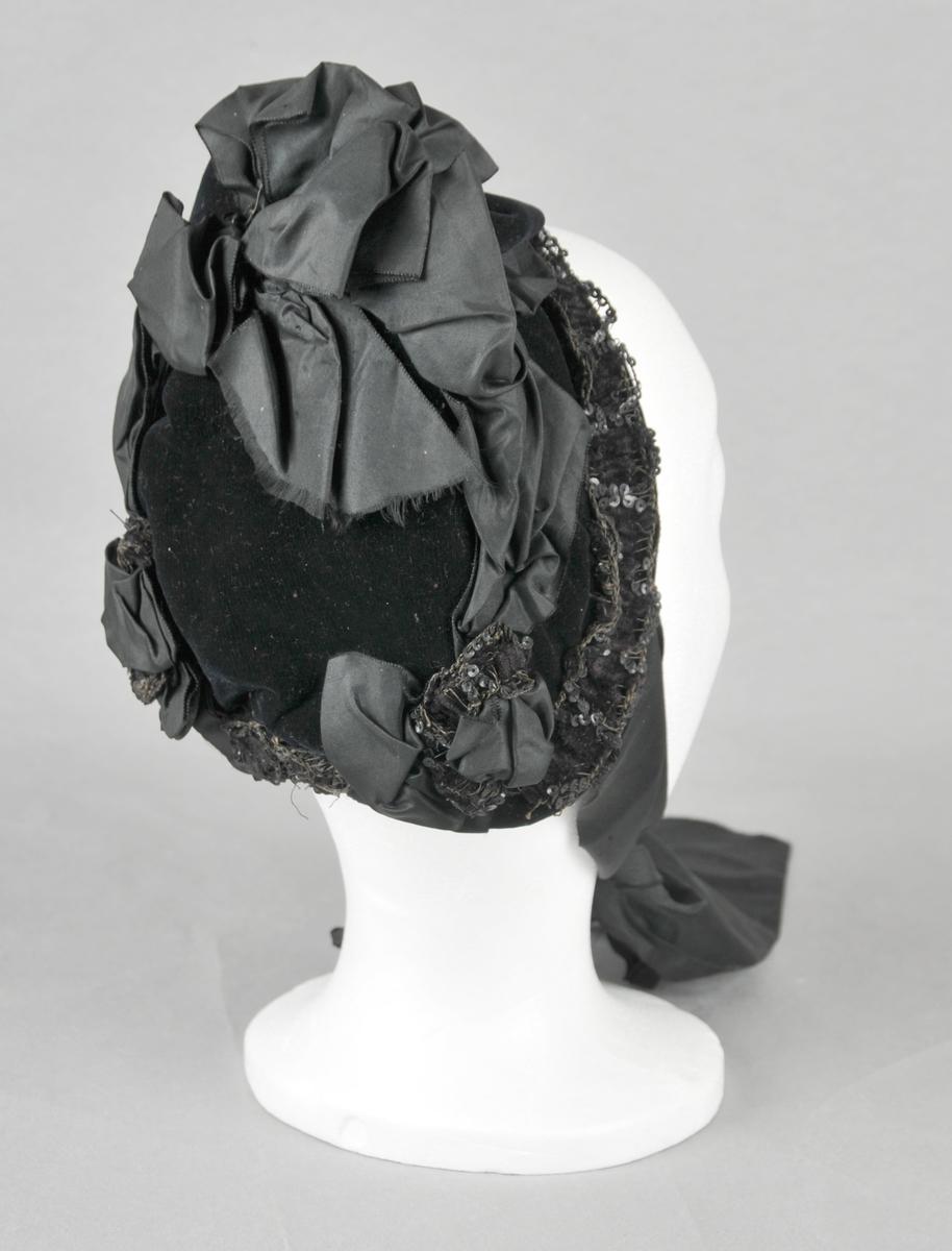 Liten, kyseforma hatt med breie knyteband. Hatten har U-form og er trekt utvendig med fløyel.Innvendig fora med tynt stoff, truleg i bomull. Kanta med breie band med små paljettar. På toppen, midt framme, silke- og fløyelssløyfe med perlepynt. Pynta elles med silkeband og sløyfer. Stiva opp innvendig med papir.