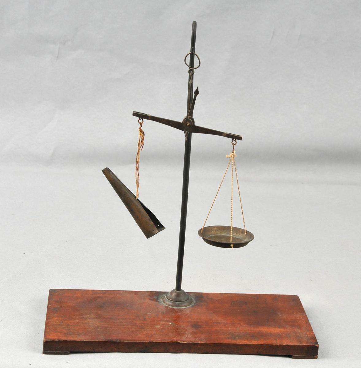Treplate med stong til å henge vekta. Skålvekt med skål hengande i eine armen og kremmarhus i andre.