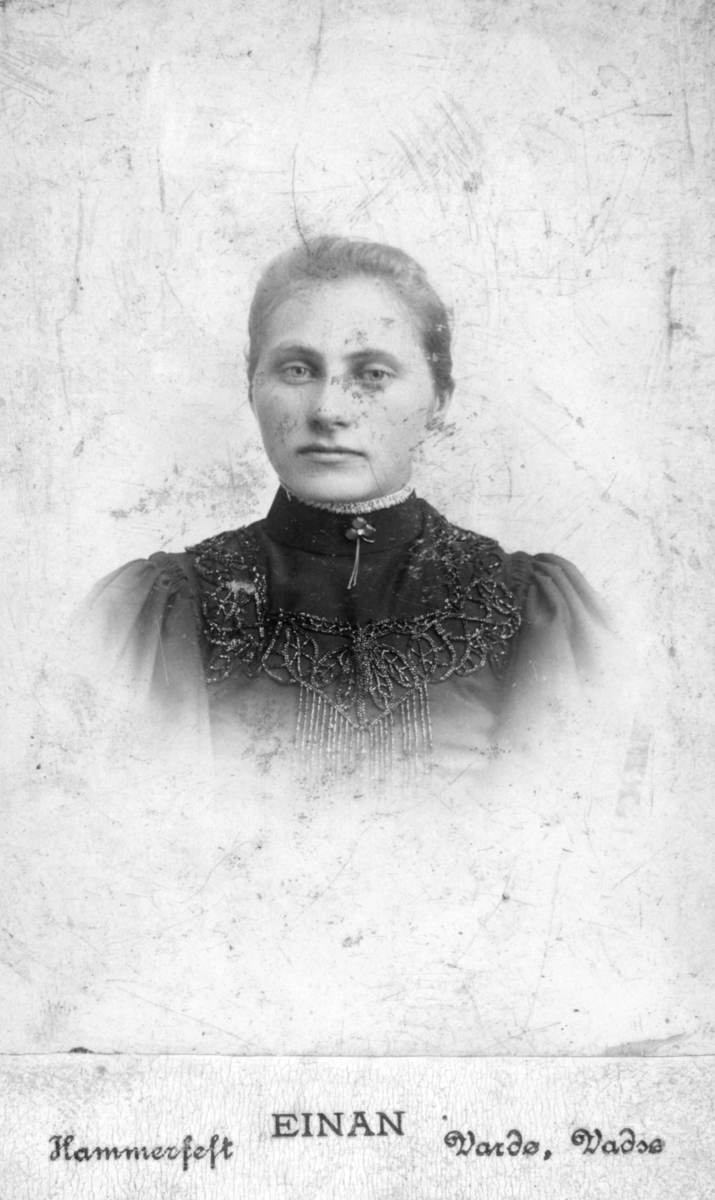 Portrett av Emilie Viktoria Nilsen, født Wanhaniemi. Hun har på seg en kjole med dekorativ bærestykke. På kragen er det festet en vakker trekløver brosje. Bildet trolig tatt mellom 1890-1900.