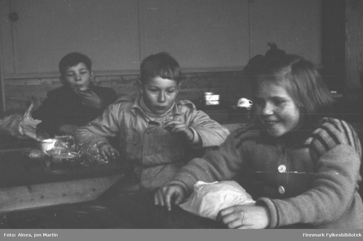 Langfriminutt med spisepause ved Øksfjord Barneskole, våren 1954. Elever med nistepakke i klasserommet, fra venstre: Jens Børve, Gunnar Rydheim og Solfrid Wilhelmsen