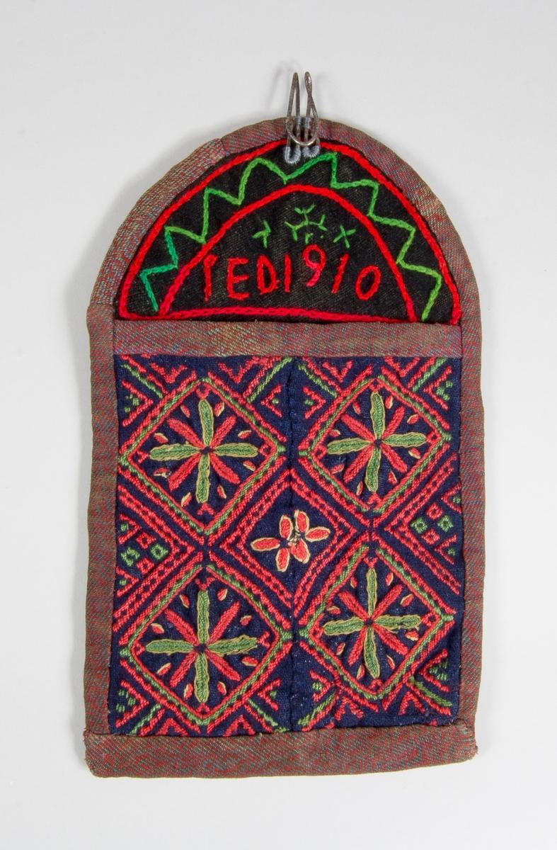 Kjolsäck till dräkt för kvinna från Nås socken, Dalarna. Modell med avskuret framstycke. Tillverkad av mörkblått ylletyg, tuskaft, kan vara handvävt, med broderi av ullgarn i rött, grönt och lite vitt. Motiv: stjärnor inskrivna i fyrkanter, trappstegslinjer, sydda med plattsöm och stjälksöm. Det är troligen två ärmmuddar som fått en ny användning. Framstycket består av två delar hopsydda lodrätt. Överstycke av svart ylletyg med enklare broderi sytt med annat ullgarn, inramning samt märkning: I E D 1910. Framstycket fodrat med handvävt linnetyg, tuskaft. Bakstycket fodrat med fabriksvävt bomullstyg, kypert, smalrandigt i vitt och lila. Kantat med remsor av handvävt bomullstyg, kypert, med olika färg på varp och inslag, rött och blått. Bakstycke av handvävt svart ylletyg, tuskaft, med broderade linjer och timglasfigur sydda med kedjesöm och läggsöm. Stor hake av ståltråd fastsydd på framsidan upptill.