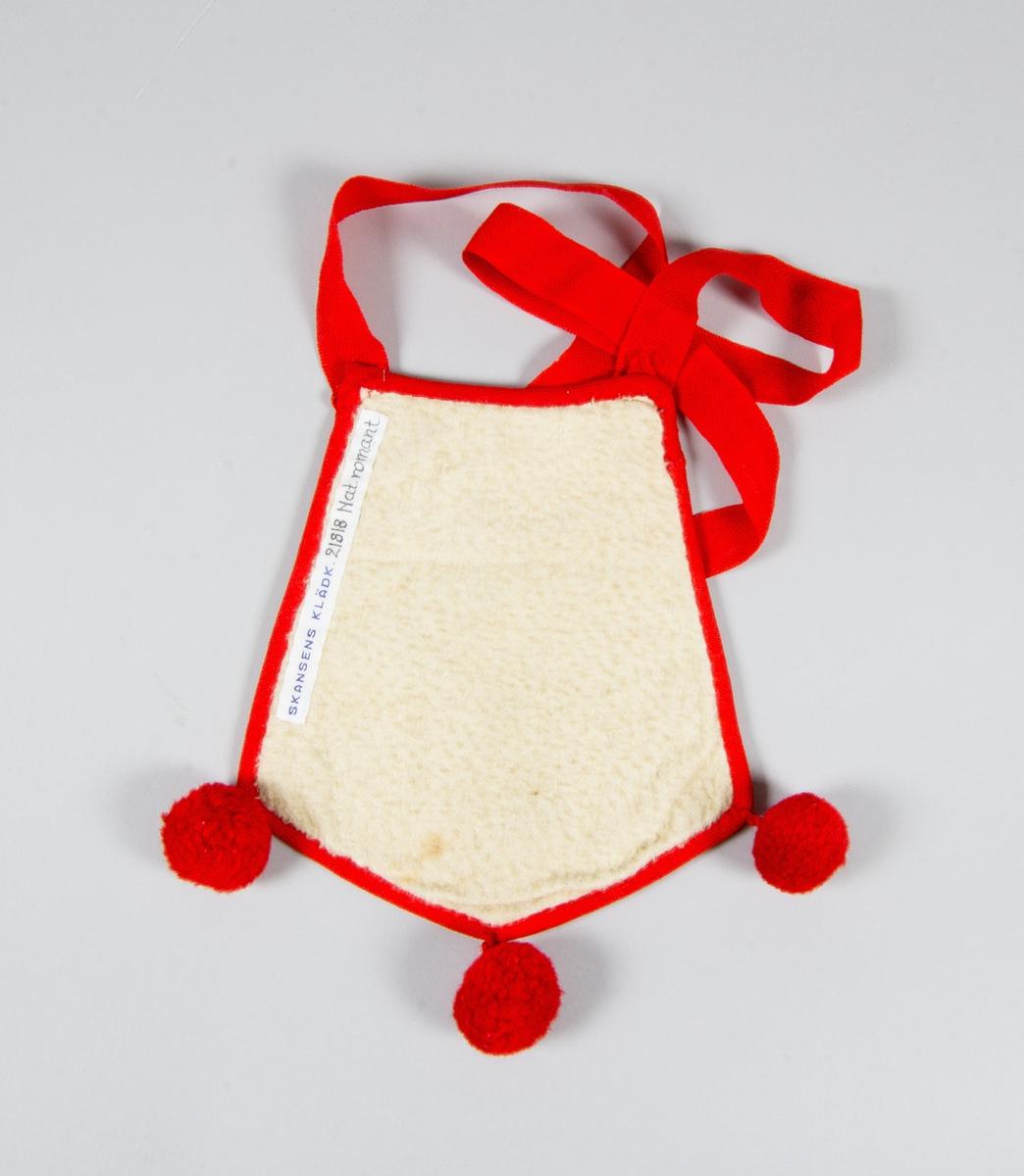 Kjolsäck, inspirerad av kjolsäckarna från Dalarna. Modell med avskuret framstycke. Tillverkad av vitt fårskinn med applikationer av ylletyg, kläde, i rött, grönt och mörkblått, fastsydda med langettsöm, gul bomullstråd. Centralt placerad hjärtblomma med rundlar och andra figurer omkring. Broderi utfört med gult och rött bomullsgarn, flätsöm och sticksöm. Kantat runtom med rött kypertvävt ylleband. Bakstycke av vit bomullsflanell. I nedre fållen tre tofsar av rött ullgarn. Axelband av spetskypertvävt rött ylleband, med tofsar av bandet vid fästena.