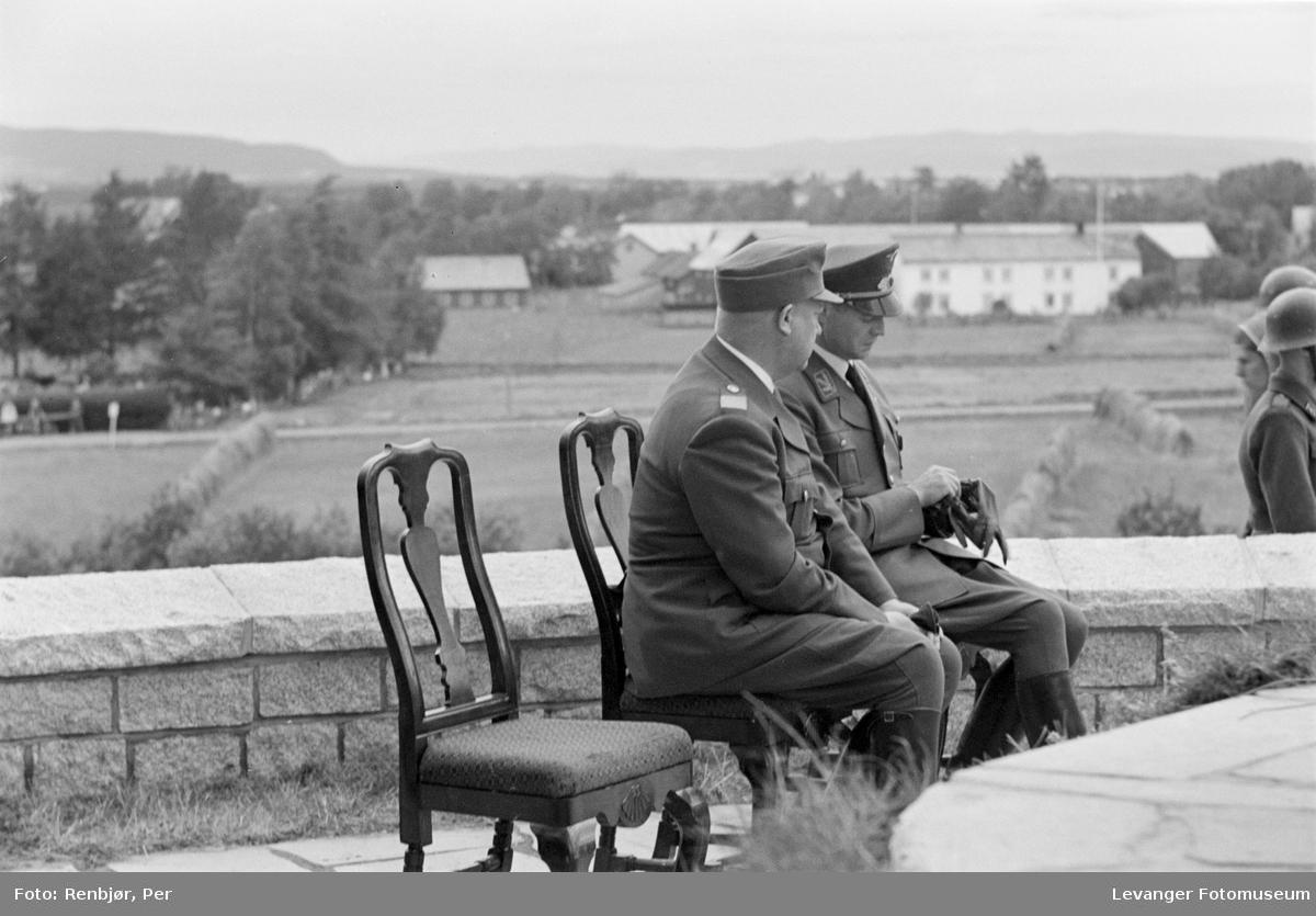 Quisling og mann i NS-partiuniform venter ved bautaen som er klar for avduking. Fra Nasjonal Samlings stevne, riksmøte, på Stiklestad 1944.