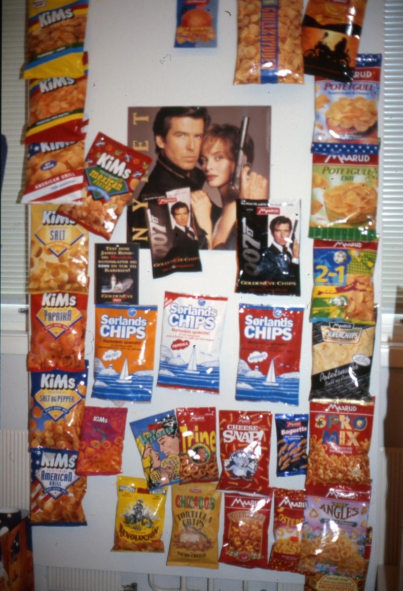 """Utstillingen """"Sjokkselgere og melkepapp"""" 1996 - 97.  Potetgullposer montert på plate. Agent 007 - plakat."""