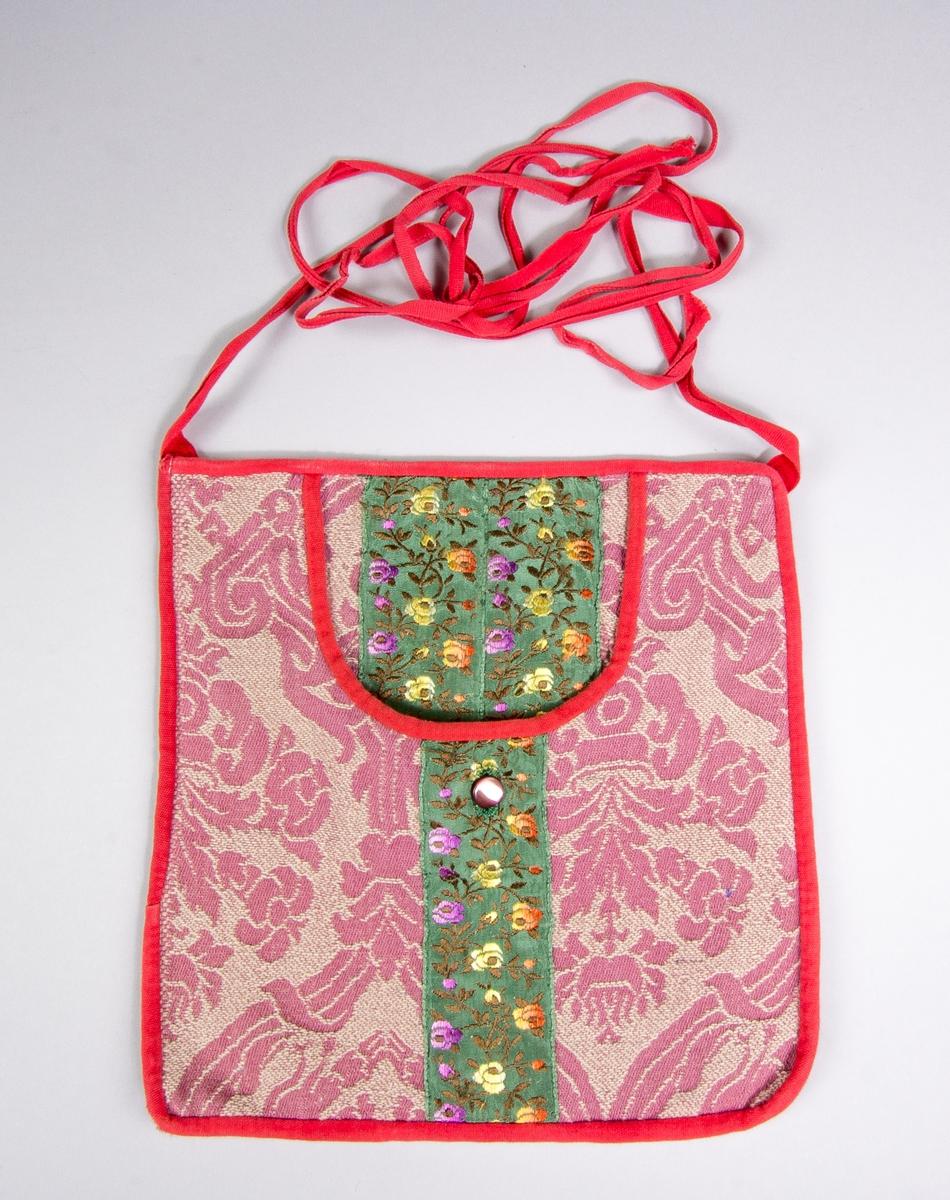 Kjolsäck till dräkt för kvinna från Västra Vingåker, Södermanland. Modell med u-formad öppning. Tillverkad av mönstrat bomullstyg, jacquardvävt, i rosa och beige. På mitten lodrätt ett sidenband påsytt, med jacquardvävda blommor i lila, gult och orange på grön botten. I öppningen syns samma tyg och band, det senare dubblerat. Liten knapp i skimrande rosa, knapphålet sytt med grön tråd. Framstycket fodrat med linnetyg, tuskaft. Bakstycke av det mönstrade bomullstyget. Kantning runtom av röda bomullsband, samma till midjeband.