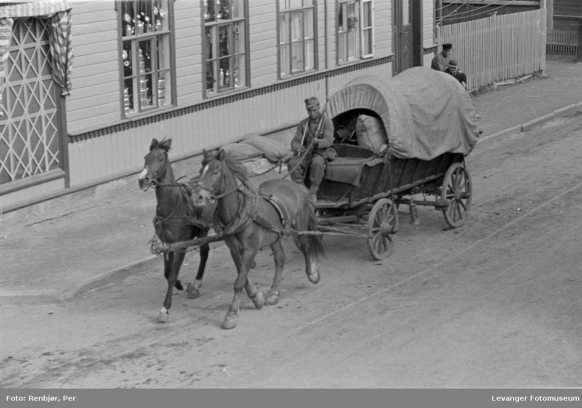 Tysk soldat kjører forsyninger med hest, bygningen bak sikret.