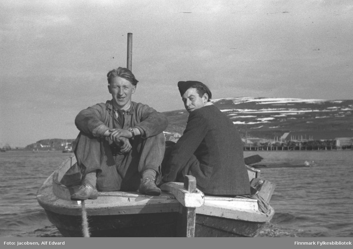 To menn på tur mot Havøysund i en åpen motorbåt, M/B Laksen som tilhørte Mathis Amundsen. Mannen til venstre på bildet er Terje Amundsen. Han har forholdsvis lyse klær og sko på seg. Et armbåndsur ses på hans venstre håndledd. Ved siden av han sitter Atle Skorpen, delvis med ryggen mot kamera. Han har en mørk jakke på seg og holder i rorpinnen med sin venstre hånd. Båten er av tre og har en hvit rekke. Et høyt eksosrør ses bak Terje. Et tau går fra hekken og mot kamera til noe de sleper. Et fjell og et nes ligger i bakgrunnen. Fjellet er Havøygavelen og neset er Innergavlodden. Det ligger noen snøflekker i terrenget og i strandkanten står en lai kai. Til venstre for M/B Laksen ses hekken på en skøyte eller sjark.