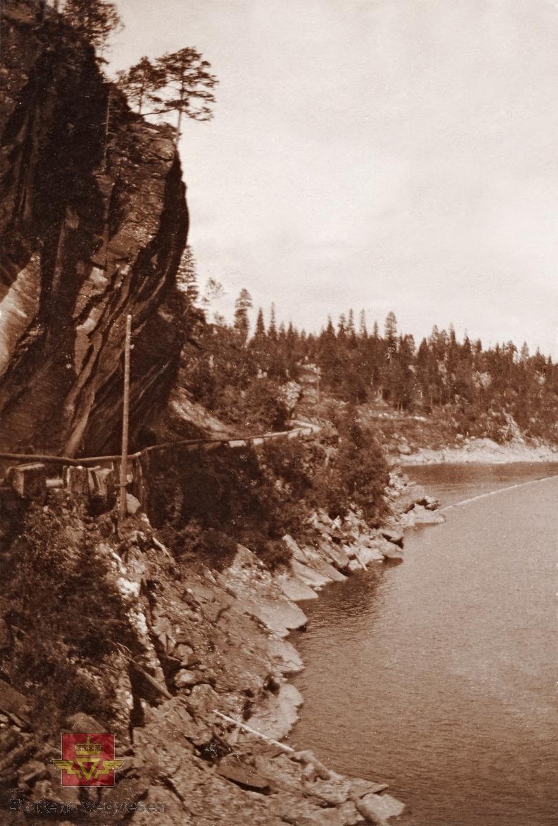 """""""Veianlæg"""". """"Klæbu langs Nidelven"""". Veg med stabbesteinrekkverk, og trestokker er festet over stabbesteinene.  18.02.2016: """"Trangfossen på Hyttefossen i Klæbu. Dette er trolig fra da veien ble bygget mellom Hyttefossen og Brøttem rundt 1885 - 1890. Vei anlagt i forbindelse med Hyttefossen sagbruk. Partiet som er avbildet ble kalt for Hengberget, og ligger på vestsiden av Båthølen i Nidelva."""" Opplysninger til bildet fra Astrid Grendstad."""